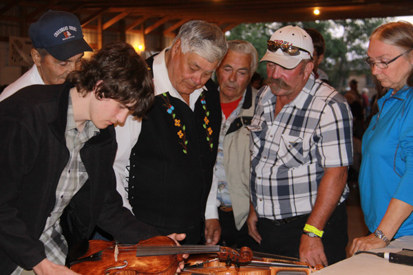 John explains to folks how his fiddles are made.