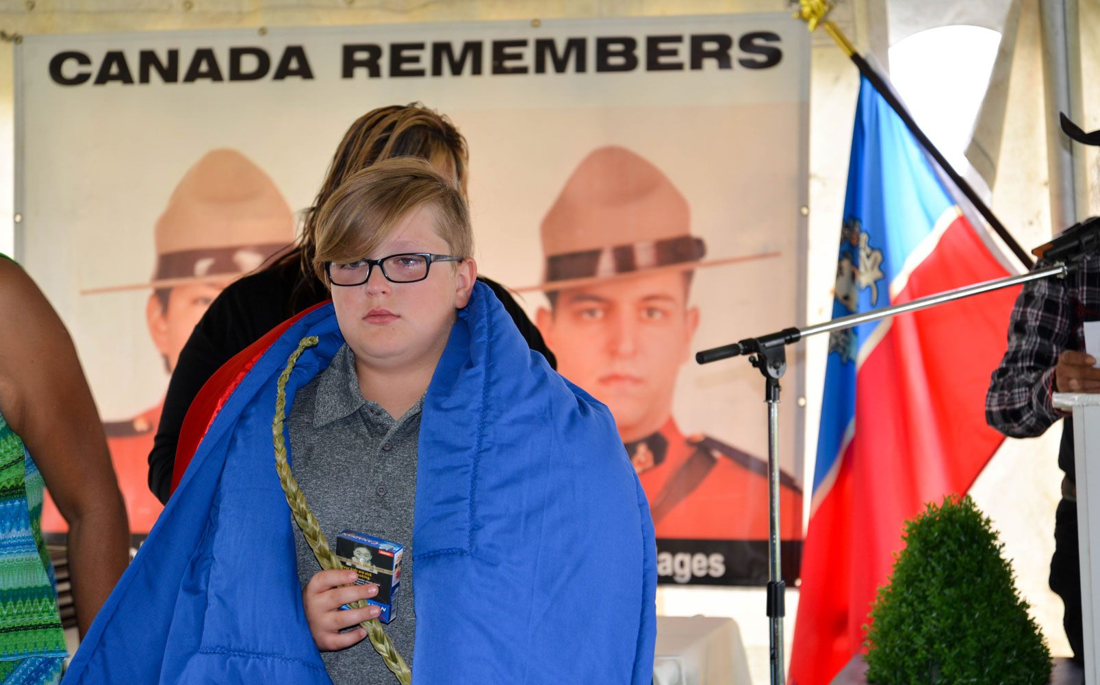 Luca was presented with a star blanket. He stands for an honour song with his father in the background.