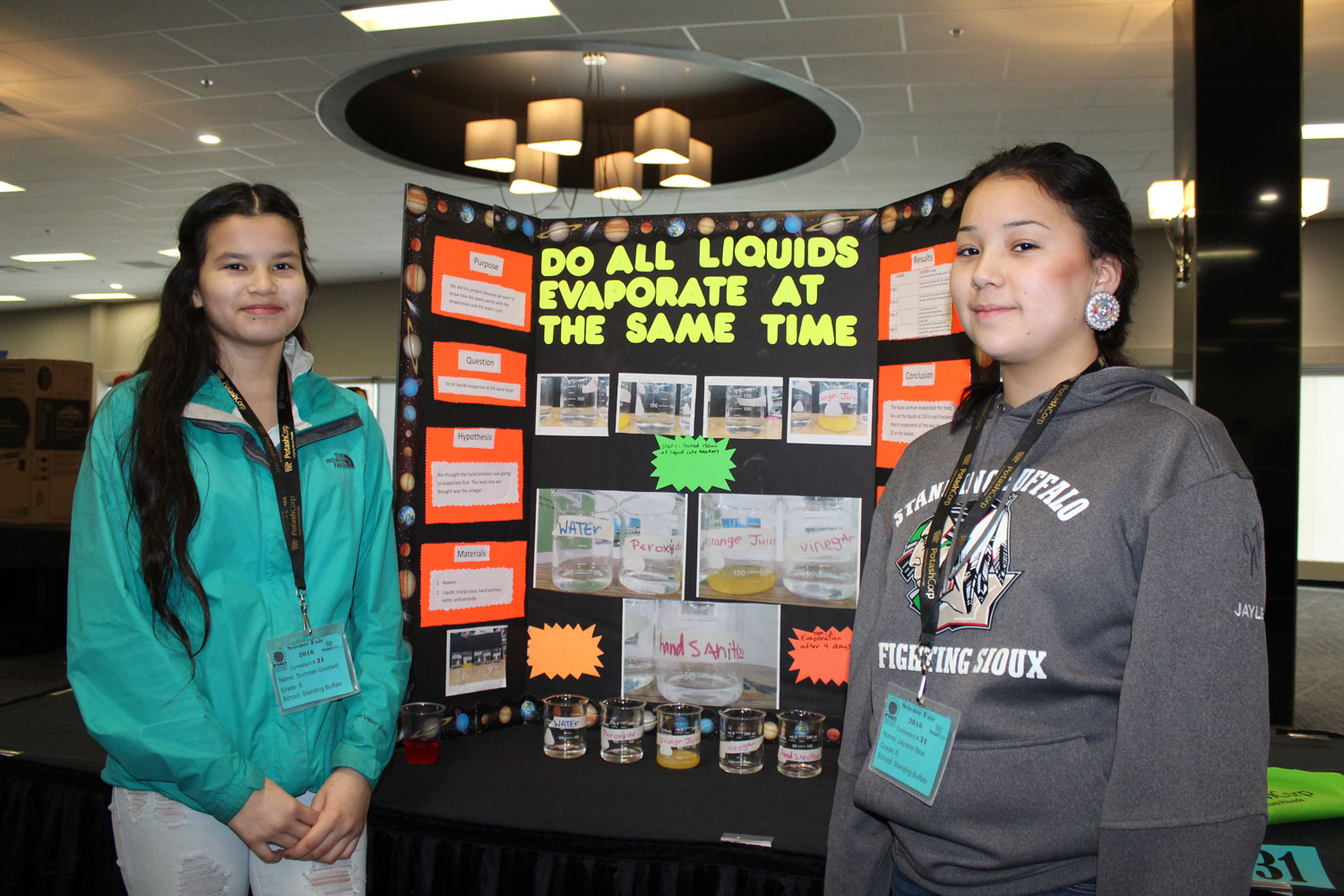 Summer Goodwill and her partner Jane stand in front of their science project. They let others know that water evaporation impacts First Nations communities.