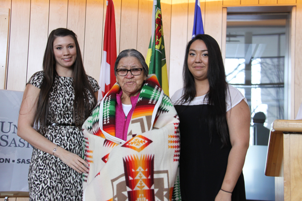 Dana Carriere, Aboriginal liaison of the U of S Graduate Students' Association and chair of the Indigenous Gradation Students' Council, and Feather Pewapisconias, president of the Indigenous Students' Council, present a blanket to Jean Oakes, widow of Gordon Oakes.