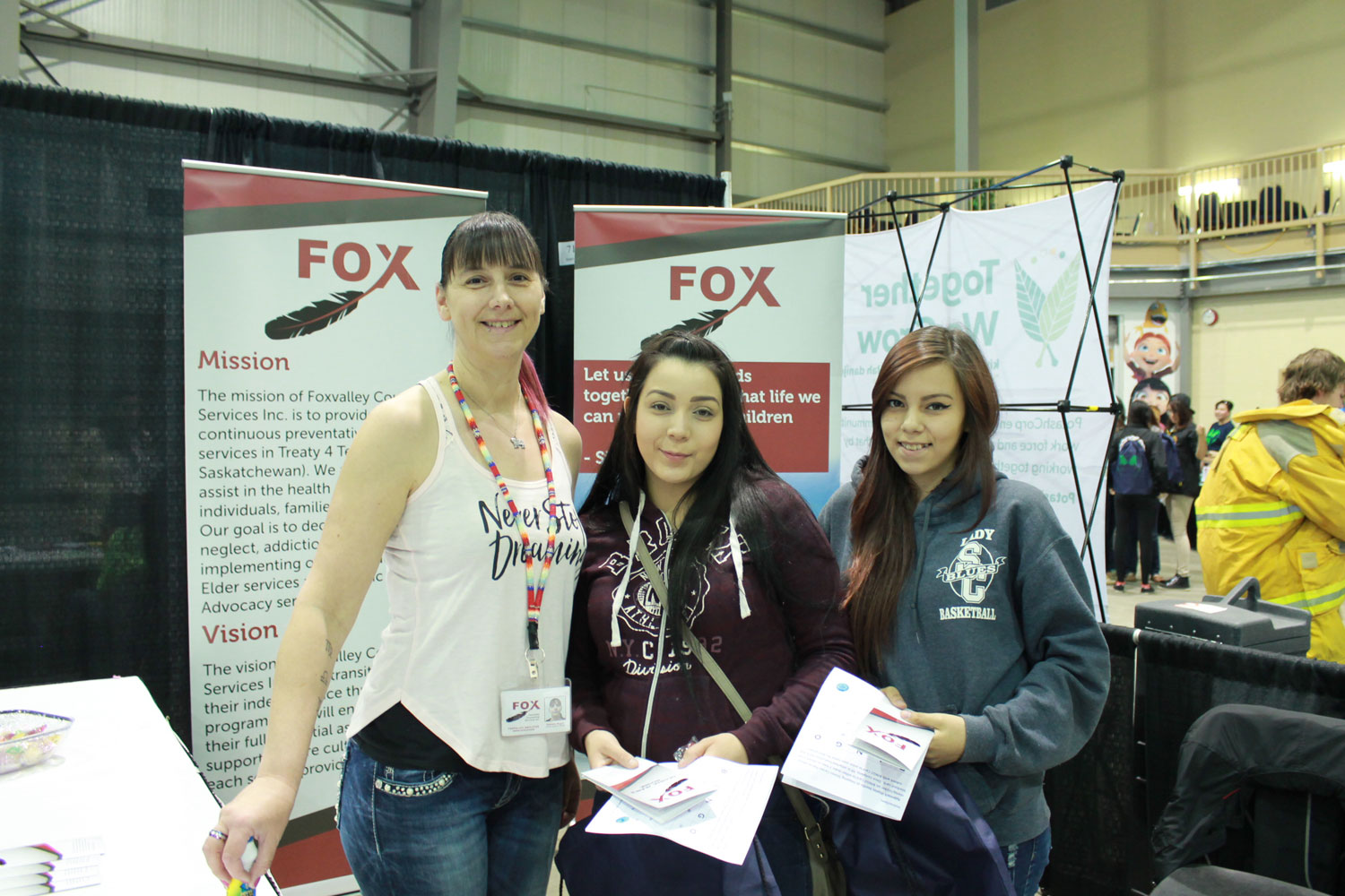 Tammy Hugette poses with two students in front of her exhibit, Foxvalley Counselling Services.