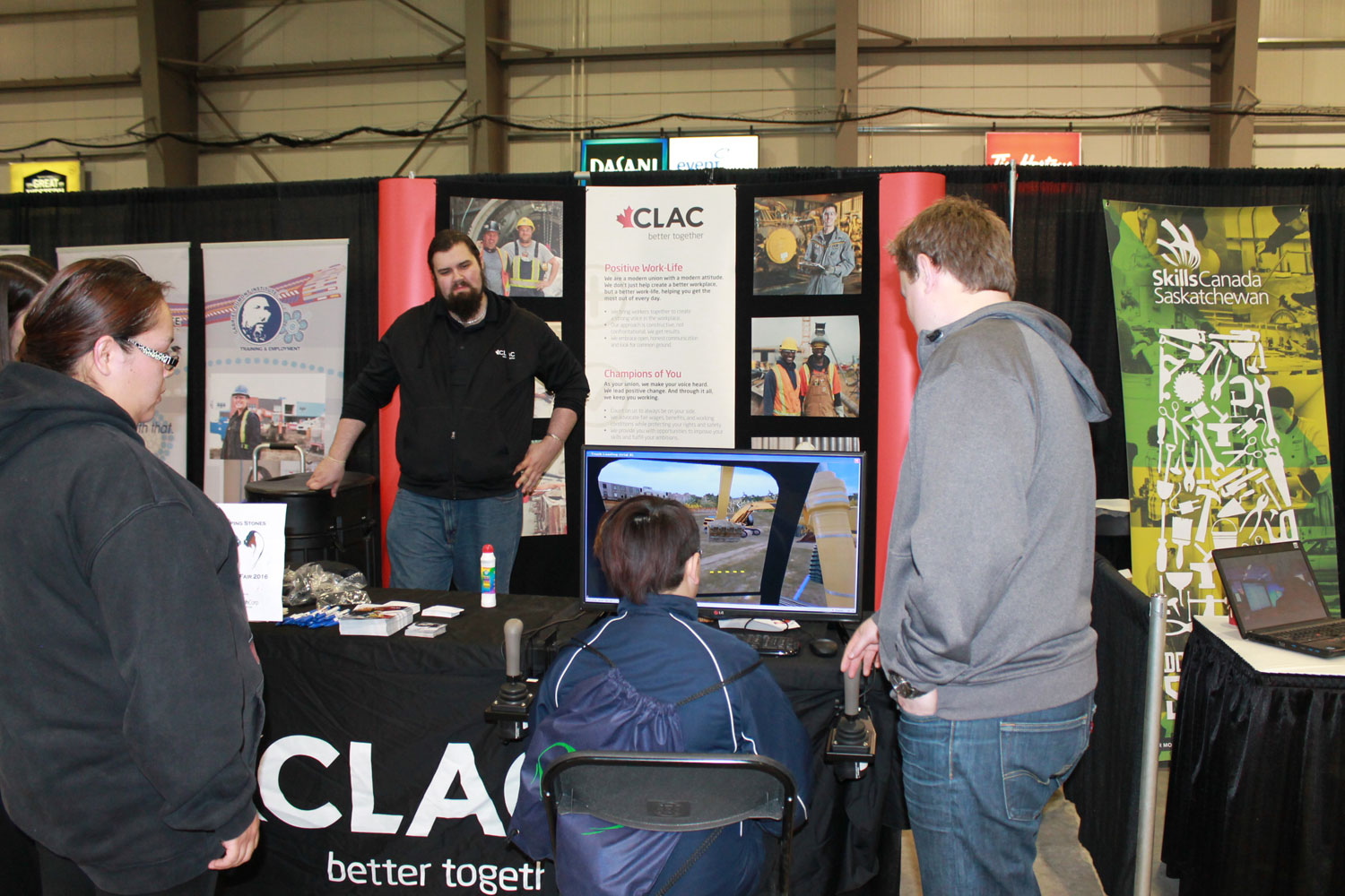 Student shown how to work a computer simulator game at the Christian Labor Association of Canada (CLAC) booth.
