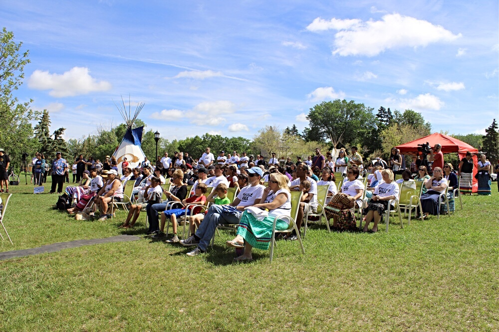 Participants listen to opening remarks at the Smudge Walk in Dewdney Park.