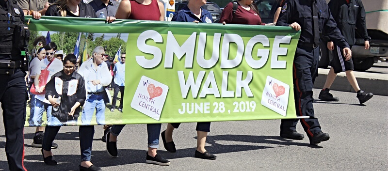 Participants in the annual Smudge Walk walk down 5th Avenue holding the year's banner.