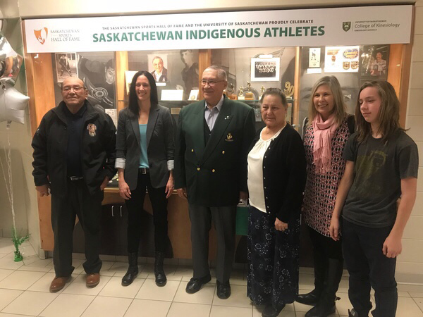 Fred Sasakamoose, Jacqueline Lavallee, Claude Petit, and family stand in front of new Indigenous athletics display at the PAC at the University of Saskatchewan.