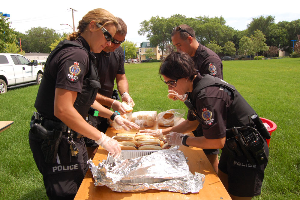Regina Police officers getting food ready for the BBQ.