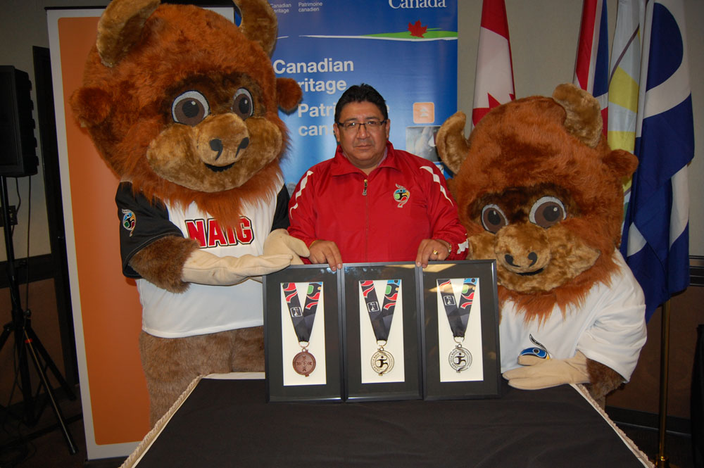 Stan Bobb (Saskatchewan First Nations CDC Association) standing with NAIG's two symbols in front of a medal showcase.