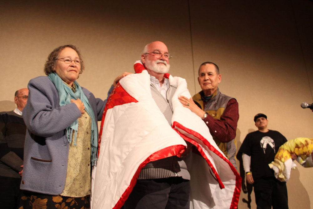 Father Gregory Boyle being honoured by Elders Maria Linklater and Mike Maurice.