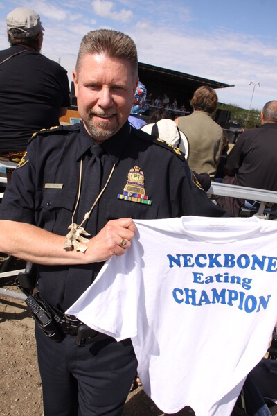 Saskatoon Police Chief Troy Cooper is now the two time defending champion in the neck bone competition. Here he shows of the t-shirt and glazed neck bone necklace he earned.
