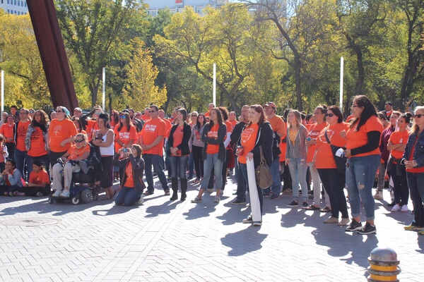 People gather in downtown Regina for Orange Shirt Day listening to guest speakers before embarking on the event walk.