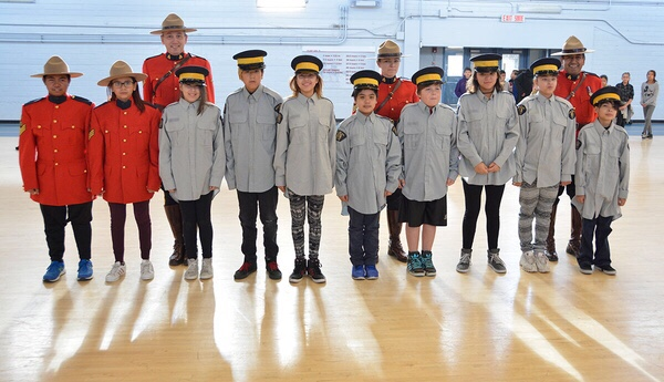 Sacred Heart students dressed in various RCMP uniforms stand at attention with Depot staff.