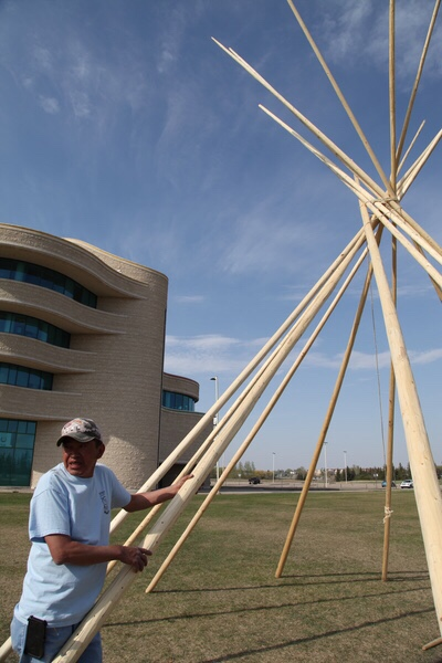 Roland Kaye says you should have good thoughts when you are setting up a tipi. He will smudge them before they are open to the public.