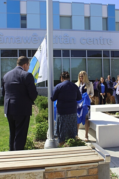 Tim Reid, President & CEO of REAL, and Tanya Foster, Regina Board of Education Trustee, hook the flags up to the pole as Isnana waits to hoist them at mâmawêyatitân centre.
