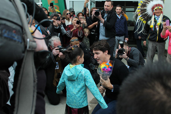 Prime Minister Justin Trudeau is greeted by 7 year old Keslee Bear from Muskapateung as she presents him with flowers.