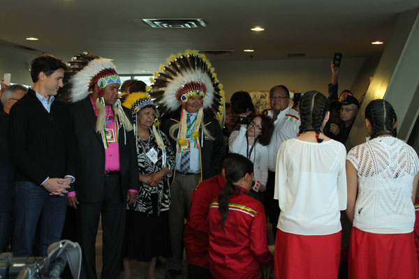 Trudeau stands with chiefs as they listen to a youth drum group.
