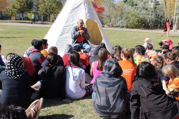 U of R elder Noel Starblanket tells stories to elementary students at the Glen Anaquod Memorial <Br>Tipi Raising Competition.