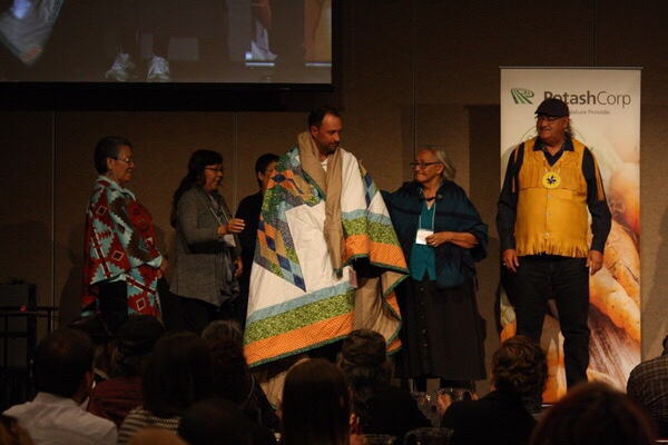 Ryan Moran, Executive Director of the National Centre for Truth and Reconciliation, presented with an honorary blanket during Wicihitowin Aboriginal Engagement Conference.