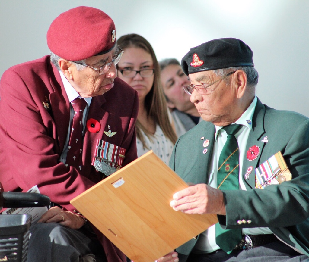 (Left) Veteran Arthur Anderson shakes his fellow veteran friend Tony Cote's hand after he received a plaque from the First Nations University of Canada.