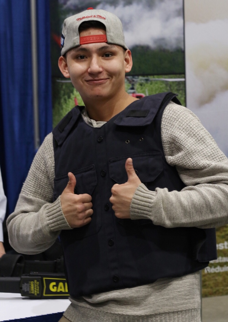 Darrell Daniels from One Arrow First Nation flashes a thumbs up after trying on a bullet-proof vest at the Future is Yours Career Expo.
