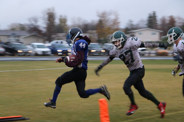 #44 Seth Sanderson, who is scoring one of his three fourth quarter touchdowns to lead the Cumberland House Islanders to a come-from-behind victory. He is pursued by #27 Shawn Francois of the Creighton Kodiaks.