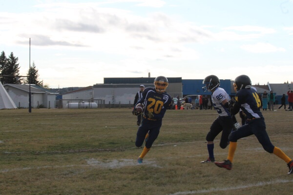 Sandy Bay player no. 20 Cory Spencer , pursued by Cumberland no. 85 Rustin Deschambeault and assisted  by Sandy bay no.14 Cornelius Whitebear.