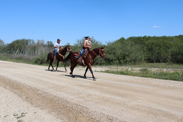 Two competitors race down the road on horseback to the Ochapowace pow-wow grounds where they had to build their own fire without using matches then as teammates, they had to fillet a fish and cook it. Teams ran with their fried fish to the powwow harbour as their finish line.