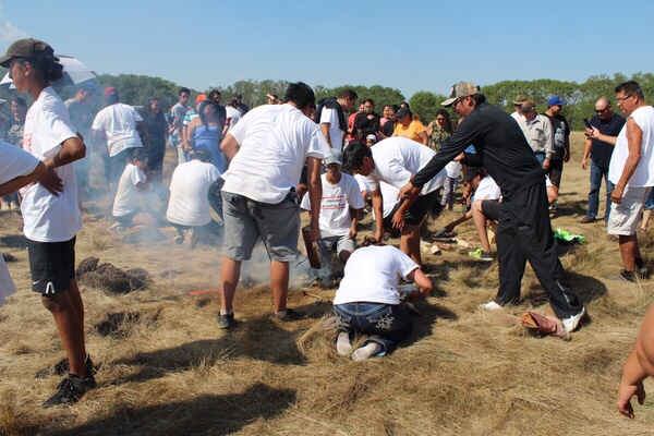 Teams gather near the powwow grounds scrambling for their last competition match where they had to build a fire, cook a fish and run into the powwow harbour handing the cooked fish to the judges.